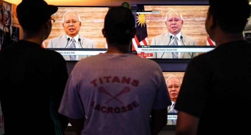 A man (C) watches televisions on display at a shopping mall store as Malaysian Prime Minister Najib Razak announces the dissolution of Parliament as he addresses the nation during a live telecast in Kuala Lumpur on April 6, 2018./AFP