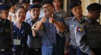 Detained Reuters journalist Wa Lone (C) gives a 'thumbs up' gesture while escorted by police in handcuffs as he arrives to court in Yangon, Myanmar,  on April 11.//EPA-EFE
