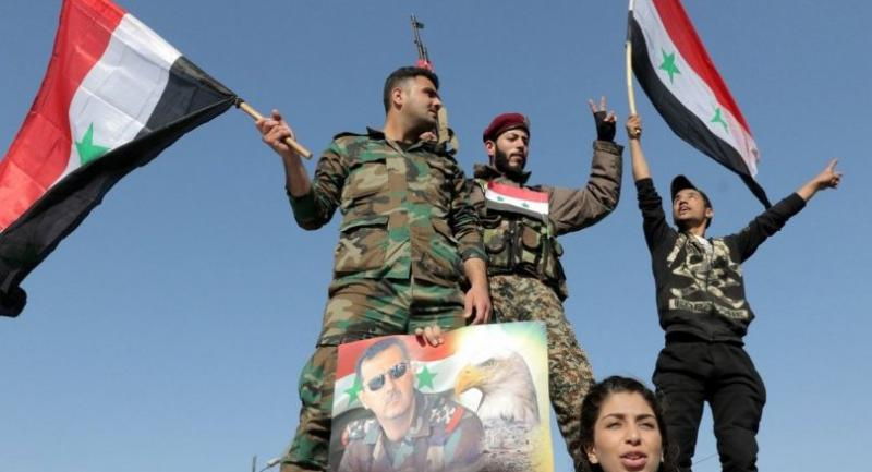Syrian soldiers and civilians wave national flags and hold photos of Syrian President Bashar Assad during a gathering in Umayyad square in Damascus, Syria, 14 April 2018. EPA-EFE