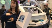 Presenter demonstrates the portable chargers kit for electric vehicle at Hong Kong Electronics Fair.
