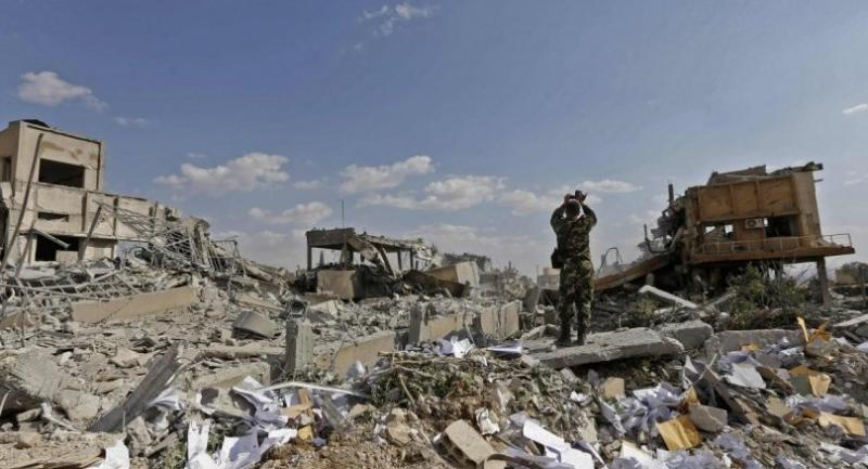 A Syrian soldier takes a picture of the wreckage of a building described as part of the Scientific Studies and Research Centre (SSRC) compound in the Barzeh district, north of Damascus. // AFP PHOTO