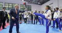 IOC president Thomas Bach holds a target for a national taekwondo exponent to kick.