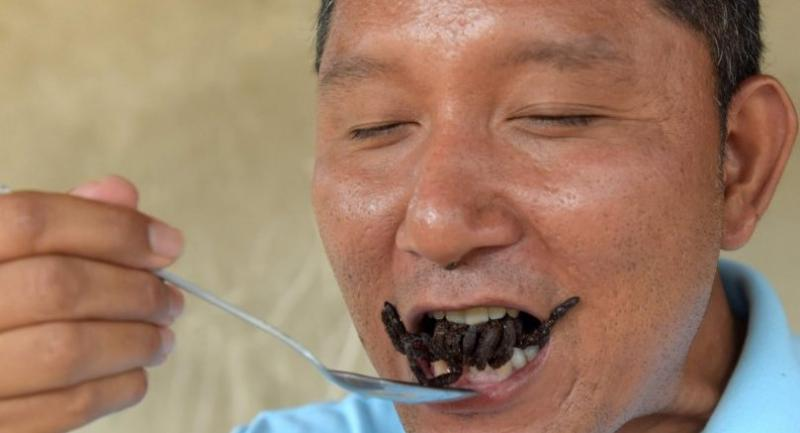 This photo taken on March 14, 2018 shows a Cambodian guide eating a fried tarantula at Skun town in Kampong Cham province. //AFP