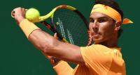 Spain's Rafael Nadal plays a backhand return to Austria's Dominic Thiem during their singles tennis match at the Monte-Carlo ATP Masters Series tournament in Monaco on April 20, 2018. / AFP PHOTO / YANN COATSALIOU