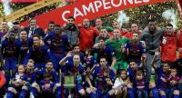 Barcelona's players pose with the trophy after winning the Spanish Copa del Rey (King's Cup) final football match Sevilla FC against FC Barcelona at the Wanda Metropolitano stadium in Madrid on April 21, 2018. Barcelona won 5-0. / AFP PHOTO