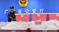 This photo taken on April 24, 2018 shows a policeman standing guard next to bags of cocaine seized in Guangzhou in China's southern Guangdong province.  // AFP PHOTO