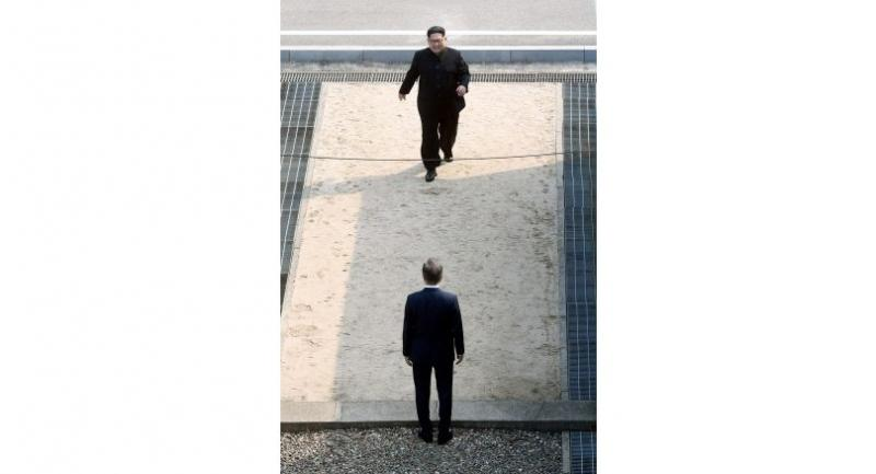 North Korea's leader Kim Jong Un (top) walks toward South Korea's President Moon Jae-in (R) as they meet at the Military Demarcation Line that divides their countries at Panmunjom on April 27, 2018./AFP