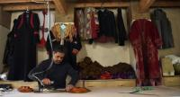 An Afghan tailor irons clothes at Zarif Design House in Kabul. / AFP