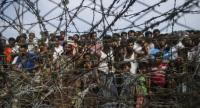 This picture taken from Maungdaw district, Myanmar's Rakhine state on April 25, 2018 shows Rohingya refugees gathering behind a barbed-wire fence in a temporary settlement setup in a