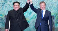 North Korea's leader Kim Jong Un (L) and South Korea's President Moon Jae-in (R) raise their jointed hands during a signing ceremony near the end of their historic summit at the truce village of Panmunjom on April 27, 2018  -AFP
