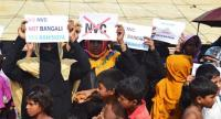 Rohingya refugees hold placards to members of United nations Security Council team during their visit to Kutupalong refugee camp in Bangladesh's Ukhia's district on 29 April 2018. PHOTO/AFP