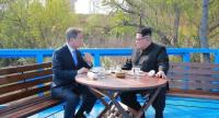 North Korea's leader Kim Jong Un (R) talks with South Korea's President Moon Jae-in (L) at a bench on a bridge next to the military demarcation line at the truce village of Panmunjom./AFP PHOTO / KCNA VIA KNS