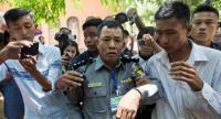 In this file photo taken on April 20, 2018 Myanmar deputy police major Moe Yan Naing (C) leaves the court following the ongoing trial of two detained journalists in Yangon./AFP