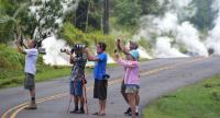 People take photos of lava as steam rises from a fissure in Leilani Estates subdivision on Hawaii's Big Island on May 4.//AFP