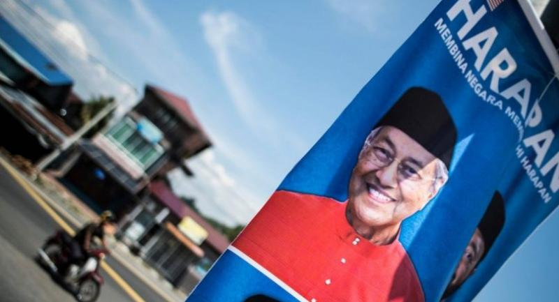 A man rides his bike past an eleddtroal poster of former Malaysian prime minister and opposition party Pakatan Harapan's candidate Mahathir Mohamad on the eve of the 14th general election in Alor Setar on May 8, 2018//AFP Photo