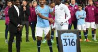 Manchester City's Yaya Toure (R) holds up an award by his brother Kolo and captain Vincent Kompany after playing for the last time for City in the English Premier League football match between Manchester City and Brighton and Hove Albion.