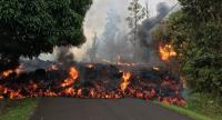 This image obtained May 9, 2018, released by the US Geological Survey shows a lava flow moving on Makamae Street in Leilani Estates at 09:32 am local time, on May 6, 2018 in Leilani Estates, Hawaii. //AFP
