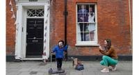 An image of Britain's Prince Harry and his US fiancee Meghan Markle is seen in a window as a woman photographs a child near Windsor Castle in Windsor, west of London on May 16, 2018. // AFP PHOTO