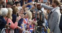 Britain's Prince Harry greets well-wishers on the street outside Windsor Castle in Windsor on May 18, 2018, the eve of Prince Harry's royal wedding to US actress Meghan Markle./AFP
