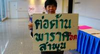 """A farmer from Lamphun protests yesterday with a sign reading """"Lamphun opposes paraquat"""" at a demonstration to oppose use of three farm chemicals. Photo Pratch Rujivanarom"""