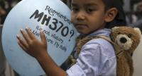 Muhammad, 4, and son one of MH370 cabin crew Mohd Hazrin Hasnan, hold a balloon during a remembrance ceremony to mark the 4th anniversary of the Malaysian Airlines flight MH370 plane's disappearance, in Kuala Lumpur, Malaysia in March.//EPA-EFE