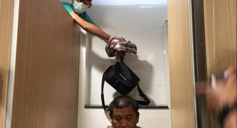 The suspect is taken by police to re-enact the crime at the shopping mall while a stand-in sits on the toilet Thursday.