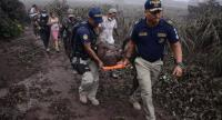 Police officers carry a wounded man after the eruption of the Fuego Volcano, in El Rodeo village, Escuintla department, 35 km south of Guatemala City on June 3, 2018. / AFP PHOTO / NOE PEREZ