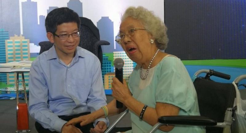 Minister to PM's Office Kobsak Pootrakool (L) touches hand with a 95-year-old woman during an opening ceremony of Future Thailand national strategy exhibition at Central World department store Wednesday.