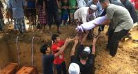 Family members and relatives hold a burial ritual yesterday for the four Muslim men who were shot dead while panning for gold at a canal in Narathiwat's Sukhirin district on Thursday.