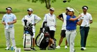 Poom Saksansin hits a shot with Panuphol Pittayarat, 1st from left, and Sarit Suwannarut, 1st from right, watching during their third round.