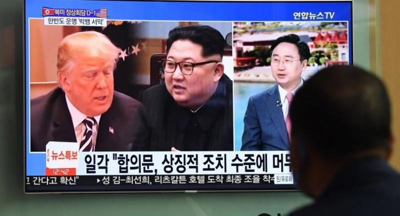 A man watches a television news screen showing US President Donald Trump (L) and North Korean leader Kim Jong Un (C), at a train station in Seoul on June 11.//AFP