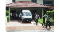 Looking for answers: Police loading boxes into a van during the raid on a house at Precinct 10 in Putrajaya.