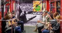 Commuters ride a World Cup themed metro car decorated with a picture of Soviet goalkeeper Lev Yashin in Moscow on June 13, 2018, ahead of the Russia 2018 World Cup football tournament. / AFP PHOTO / Yuri KADOBNOV
