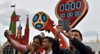 People take selfie pictures, with their mobile phone, in front of the digital FIFA World Cup 2018 countdown clock placed near the Red Square and the Kremlin, in Moscow.
