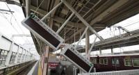 Train guide electric boards tilt following an earthquake at Ibaraki-shi Station in Ibaraki City, north of Osaka prefecture on June 18.//AFP