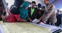 Family members of missing passengers look at a list of names at the Lake Toba ferry port in the province of North Sumatra on June 20, after a boat capsized on June 18.//AFP
