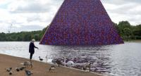 """A woman feed birds in front of """"The London Mastaba"""" by Bulgarian artist Christo Vladimirov Javacheff, usually referred to only as Christo. /AFP"""