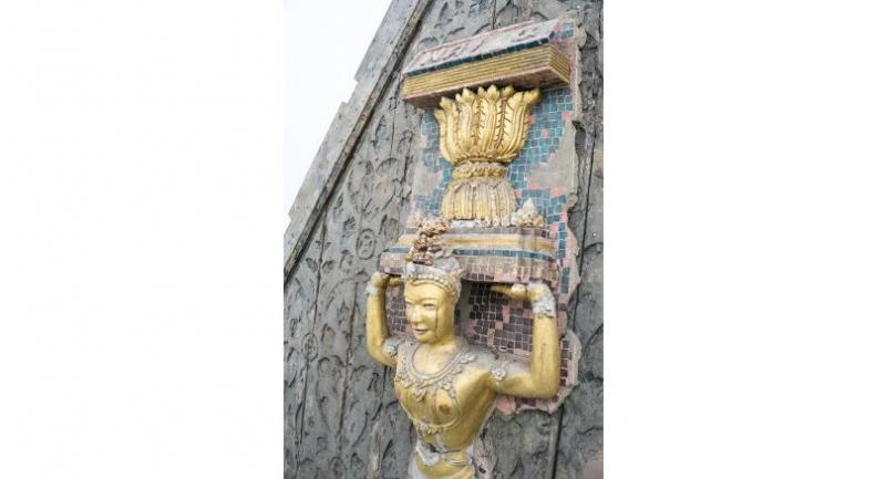The stunning  old wooden pediment featuring a deity holding an image of the symbolic constitution from Wat Trimitr is among the highlight at