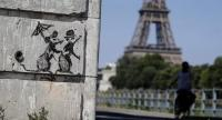 A recent artwork by street artist Banksy is pictured near the Eiffel Tower./AFP