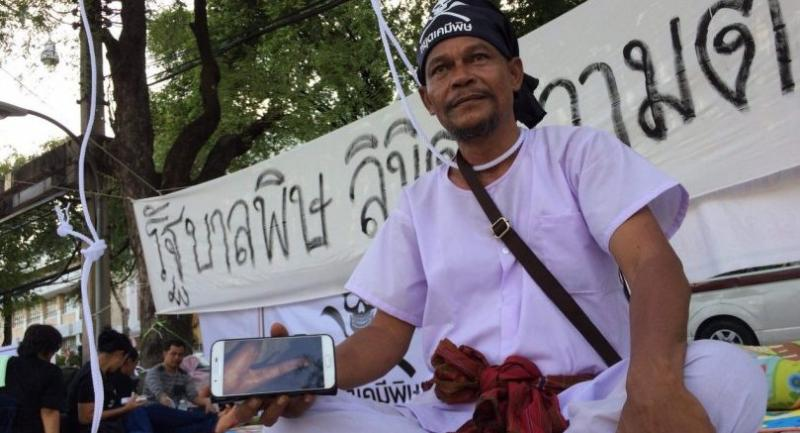 Amnart shows a photo of his infected hand at the recent protest against paraquat.