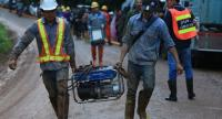 Workers carry a pumper to be used in pumping flood water out of Tham Luang Cave in Chiang Rai's Mae Sai district in a bid to rescue a team of 12 young footballers and their assistant coach trapped inside the cave since June 23.