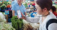 A woman scans QR code with her mobile to pay for vegetable at the stall of Jiang Gou Fang, left, at Wen'Er street vegetable market in Hangzhou. Photo by Poon Sook Yee