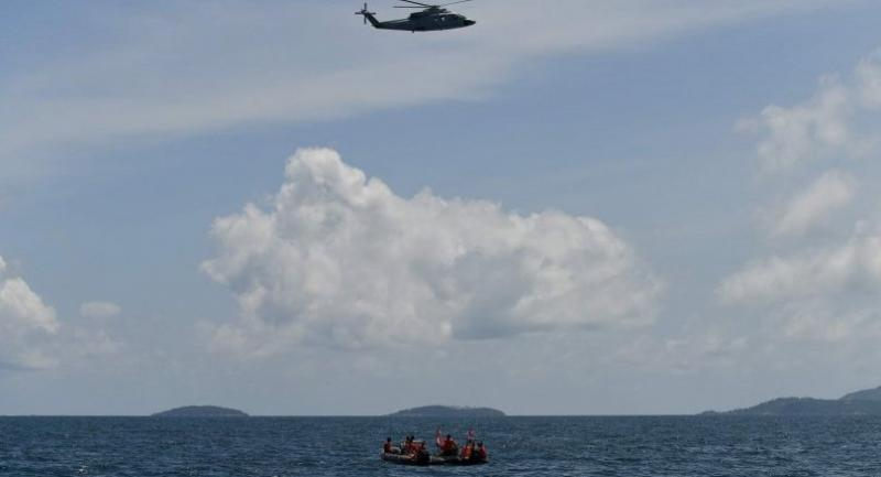 A helicopter and rescuers search an area near Phuket on July 7, 2018, as rescue operations continue for missing tourists following a boat accident on July 5.//AFP
