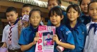 Younger pupils at Chiang Rai's Ban Wiangphan School show a schoolbook of good deed records with the picture of Mathayom 2 student Adul Sam-on, 14.