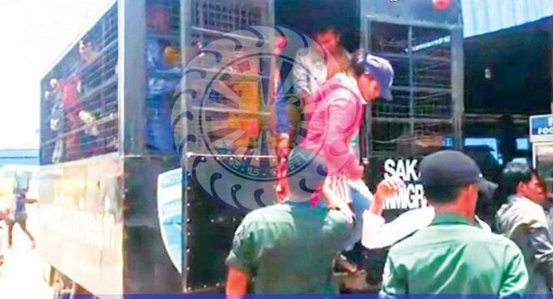 Cambodian immigration officers help deportees board a bus to return them to their provinces.//Photo : national police