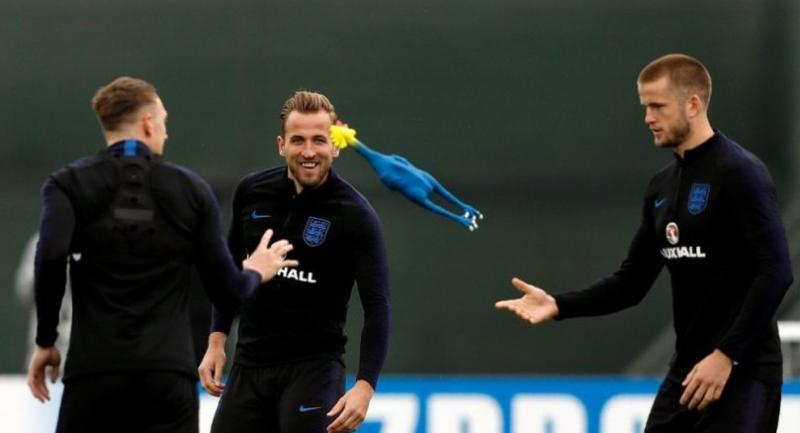 England's defender Phil Jones (L), forward Harry Kane (C) and midfielder Eric Dier (R) throw a toy rooster as they take part in a training session.