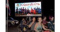 Motorists in Chiang Rai pass a billboard with a photograph showing members of the Thai boys' team and their coach with a message