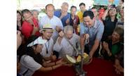 Chua Lam (seated, third from left) was invited to pry open a durian. Second from right is orchard owner Su Jian Xing