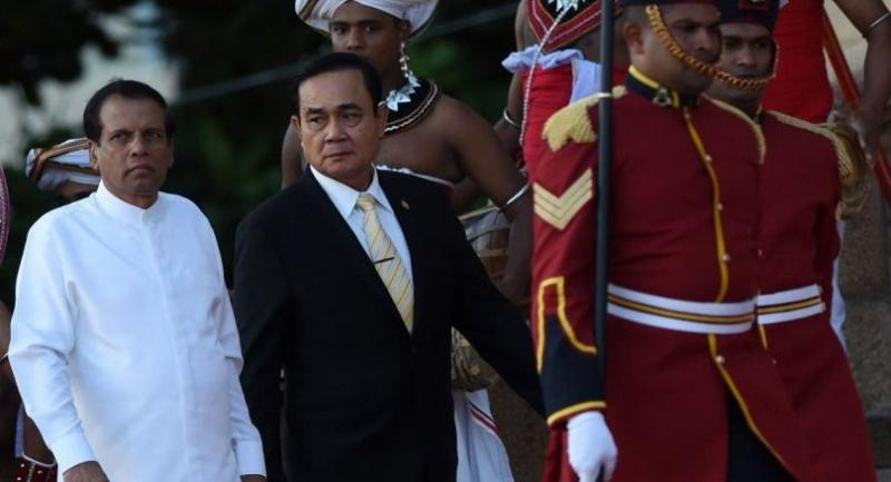Thai Prime Minister Prayut Chan-o-cha (C) walks with Sri Lankan President Maithripala Sirisena (L) during a welcoming ceremony at the Presidential Secretariat in Colombo on July 12, 2018. /AFP