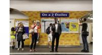 People take pictures of a sign reading 'We have two stars' ('On a deux etoiles') at the Etoile metro station in Paris metro on July 16, 2018 one day after France won the Russia 2018 World Cup final football match.//AFP